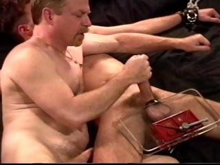 Chap in leg and feet restraints receives his cock and balls smashed by his slaver