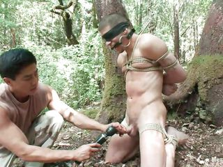 Watch Roderick being fastened up, blindfolded and throat gagged in the middle of the forest. He is stripped and his wet cock is taunt with a vibrator after this man gave it a mean rub. Wonder what else this chab will do to him, it will be a shame not to take advantage of his hot stripped body as they are alone in the woods.